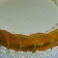 torta decorata con panna e fette di arancia
