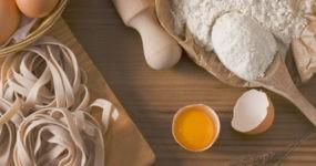 Uovo aperto con accanto farina, tagliatelle e mattarello